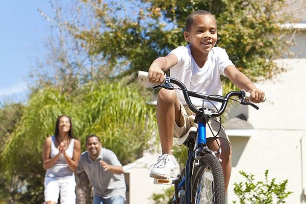 Biking child with cheering parents